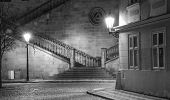 Old, ancient city in night, shining lantern, stairs, BW