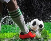 Soccer Football Players Kicking To Soccer Ball On Green Grass Field With Splashing Of Transparent Wa