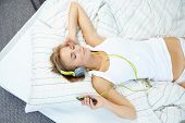 Blonde woman lying on bed while listening music through headphone