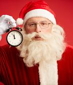 Happy Santa with alarm clock showing five minutes to midnight