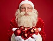 Portrait of Santa holding red decorative toy balls
