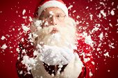 Santa Claus blowing snow and looking at camera