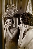 Stunning vintage 1920s woman looking in an antique mirror