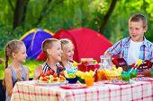 Happy Kids Around Summer Picnic Table