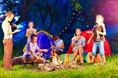 pic of bonfire  - happy kids playing around bonfire in summer camp - JPG