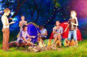 foto of bonfire  - happy kids playing around bonfire in summer camp - JPG