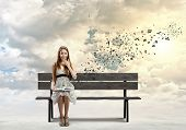 Asian pretty woman sitting on bench and reading book