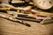 a stained brush, colored pencils of different colors, a pair of eyeglasses and an old clock on a tab