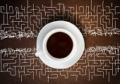 Close up of cup of coffee and labyrinth at background