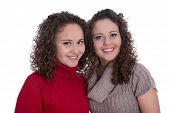 Siblings: Two Monozygotic Young Twin Womans In Portrait Isolated Over White.