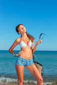 Outdoor fashion portrait of young sensual happy woman with jeans shorts and bag on the beach. Enjoyi