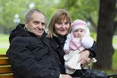 Great-grandfather, Grandmother And Little Baby Girl On A Bench In The Park