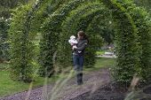 Mother And Baby Walking Through An Ivy Overgrown Archway