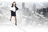 Young businesswoman walking on rope with blank banner