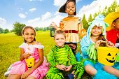Happy children in Halloween costumes sit on grass