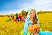 Girl in monster costume holds Halloween pumpkin