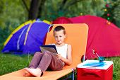 Young Boy In Summer Camp, Relaxing With Tablet