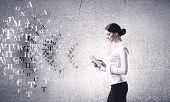 Young woman holding tablet pc in hands and letters flying around
