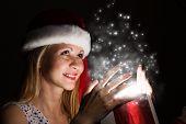 Happy woman in santa hat opening Christmas gift box