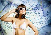 Young pretty girl in white bikini and headphones