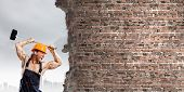 Strong man in uniform breaking brick wall with hammer