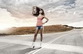 Young pretty woman tourist with suitcase with suitcase on shoulder