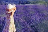 Little girl in a white hat looking at the lavender field