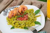 A Plate Of Spinach Pasta With Shrimps And Tomato Sauce