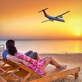 Couple in hug watching airplane flying into the sunset