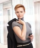 Attractive elegant caucasian businesswoman with mobile phone in hand at office, jacket on shoulder.