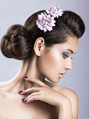 Beautiful girl with perfect skin and purple flowers on her head.