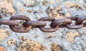Heavy Rusty Chain Over Stone Wall