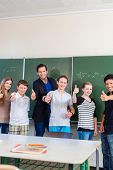 School and education - Teacher and students stand in front of a blackboard with math work in a class