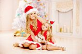 Mom and daughter dressed as Santa celebrate Christmas. Family at the Christmas tree. Woman and girl
