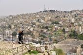 AMMAN, JORDAN - MARCH 17, 2014: Tourists admire the view to the Roman Theatre from the Citadel hill.