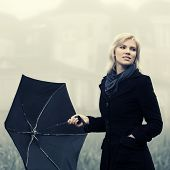 Young fashion woman with umbrella in autumn foggy morning