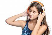 Beautiful hispanic teenage girl enjoying music on bright orange headphones isolated on white