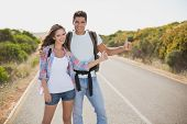 Portrait of young couple hitchhiking on countryside road