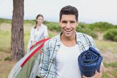 Portrait of a happy young couple with tent walking on countryside landscape