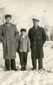 SIERADZ, POLAND - CIRCA FIFTIES: Vintage photo of grandfather, father and son outdoor in winter.