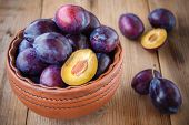 Organic Ripe Plums In A Clay Bowl