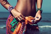 young woman on beach tiedown colorful sarong wearing beautiful braceletes