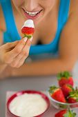 Closeup On Happy Young Woman Eating Strawberry With Yogurt In Ki