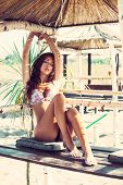 attractive tanned young woman in bikini relaxing on wooden bench on the beach