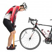 Asian cyclist pumping air to bike tire, using manual air-pump, isolated on white background.