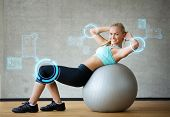 fitness, sport, training, future technology and lifestyle concept - smiling woman with exercise ball in gym over virtual screen projections