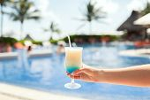 vacation, beverage and travel concept - close-up of female hand holding glass with cocktail