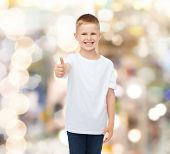 advertising, gesture, people and childhood concept - smiling little boy in white blank t-shirt showi