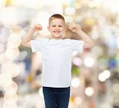 advertising, gesture, people and childhood concept - smiling little boy in white blank t-shirt ith r