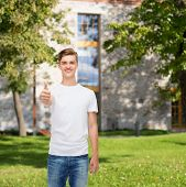 gesture, advertising, summer vacation, education and people concept - smiling young man in blank whi